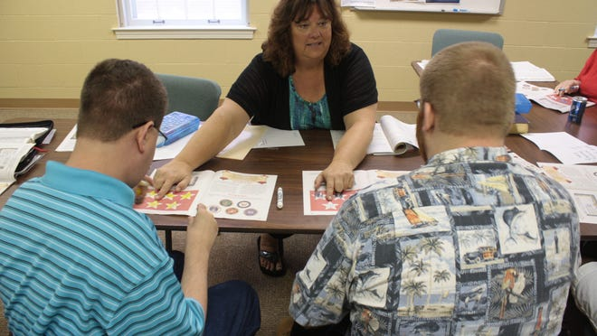 Laura Riddell teaches a Bible story to Joe Eastman, left, and Ben Gillespie in the adult Special Buddies class at Englewood Baptist Church in Jackson.