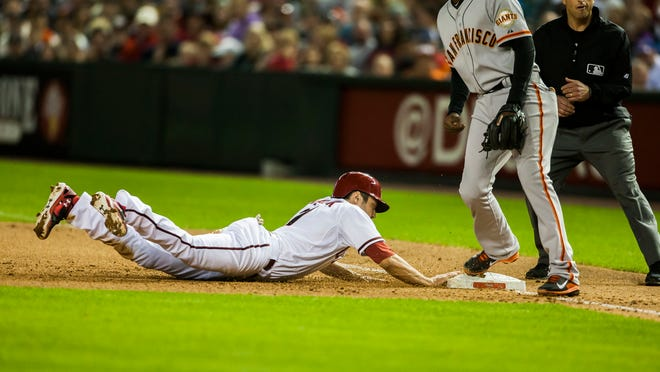 Diamondbacks baserunner A.J. Pollock dives back to first base during a game against the Giants on Tuesday, April 1, 2014, at Chase Field in Phoenix.