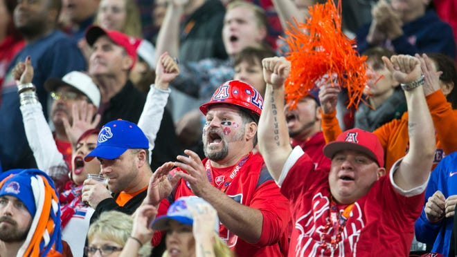 It was a relatively short trip to the Fiesta Bowl for many UA fans, but not for Marvin Cassler (middle, wearing hardhat), who came from Salt Lake City to cheer on the Wildcats.