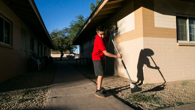 Carlos Real, 10, helps out his mother by doing daily chores at Casa De Esperanza apartment complex. These apartments are owned by the city of Chandler and are reserved specifically for low-income individuals and families through its public housing program.