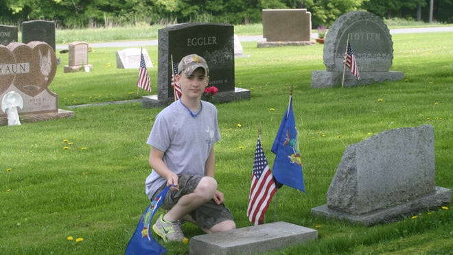 Darren Johnstone places flags on the grave of Trooper Richard A. Van Alstyne in White Sulphur Springs in 2013.