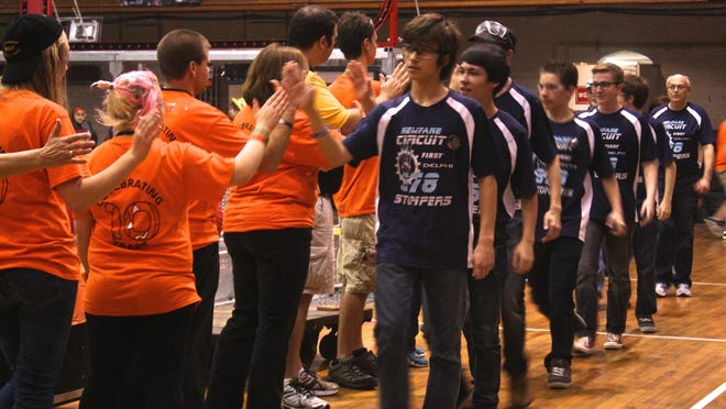 Newfane High school sophomore Kyle Krause, right, leads his winning robotics team at the Rah Cha Cha Ruckus Robotics Competition awards ceremony.