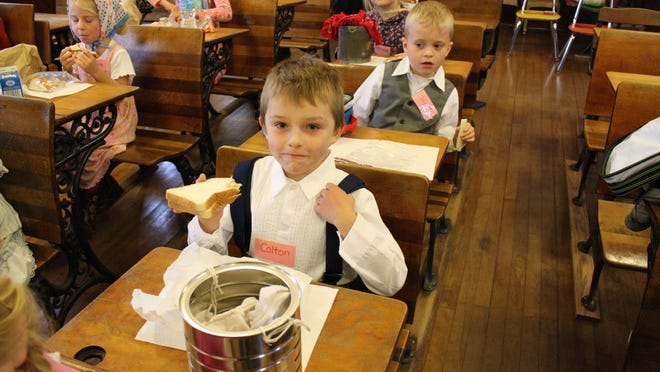 Students from Robin Hein's first-grade class at Jefferson School chow down on lunches prepared in tin pails.