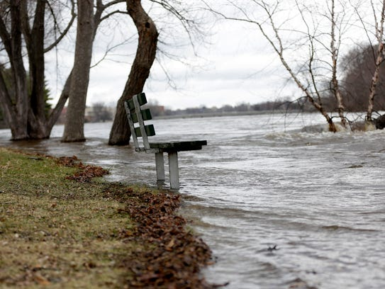 Floodwaters brush up to a bench that overlooks the