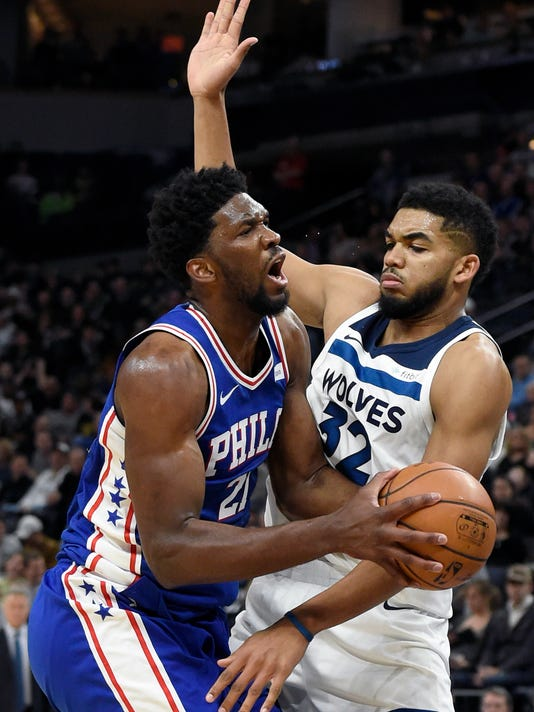 Philadelphia 76ers center Joel Embiid (21), of Cameroon, drives against Minnesota Timberwolves center Karl-Anthony Towns (32) during the second quarter of an NBA basketball game on Tuesday, Dec. 12, 2017, in Minneapolis. The 76ers won 118-112. (AP Photo/Hannah Foslien)