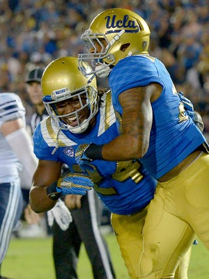 UCLA's Nate Starks (right) hugs running back Paul Perkins after Starks scored in the fourth quarter Saturday.