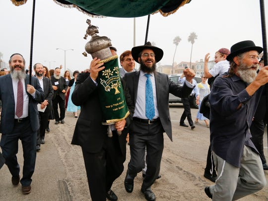 Rabbi Dov Muchnik, center, dances in a procession with a World War II-era Torah as the members of Chabad of Oxnard take part in a dedication ceremony last month. The Torah was rescued from Eastern Europe during World War II.