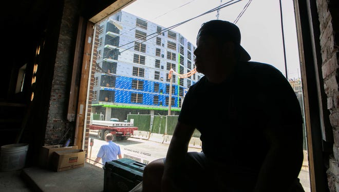 Stitch House Brewery owner Dan Sheridan sits in the back of his brewery this week with the $75 million Residences at Mid-Town Park behind him.