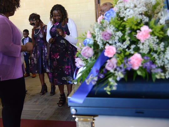 "Joan Namachemo, the wife of Matanda ""Mike"" Wasike, who died after nearly five years of trying to recover from a beating, dances with family and friends Saturday during a service memorializing his life at Imani Family Church in West Des Moines."