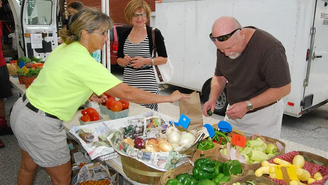 Marty Wood of Scott Farms sells produce to Tatiana and Patrick Nettles of Independence during the Independence Farmer's Market in July of 2014.