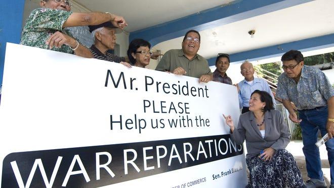 In this March 2010 file photo, from left, Leonard Aguigui, Tom Barcinas, Evelyna Akimoto, Sen. Frank Blas Jr., Tony Lujan, Piti Mayor Ben Gumataotao, former Sen. Telo Taitague and Jose Taitague show a war reparations billboard at Lujan's house in Anigua.