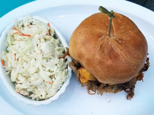 Sneaki Tiki's Kahlua pulled pork sandwich is slow-cooked meat with Hawaiian sea salt, tossed in a citrus barbecue sauce with melted cheddar on a brioche bun. It was served with a side of crisp, fresh coleslaw.