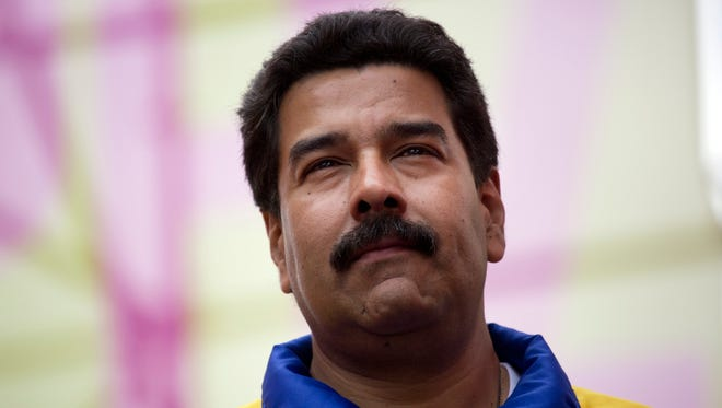 Venezuelan President Nicolas Maduro looks at his supporters during a motorcycle rally in support of his government, in Caracas, Venezuela, Monday, Feb. 24, 2014.