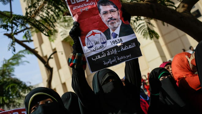 "A supporter of Egypt's ousted President Mohammed Morsi holds an old presidential campaign poster of him with Arabic that reads, ""Mohammed Morsi, president for Egypt, 2012, resurrection is the will of the people,"" during a protest a day before the trial of the former president in Egypt, Sunday."