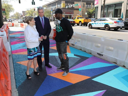 "Janet Langsam of ArtsWestchester, White Plains Mayor Thomas Roach and artist Wayne ""Wane One"" Peterkin chat last Sunday by the mural he is painting on Mamaroneck Avenue. The artist was awarded a public art commission from ArtsWestcheter to paint the mural in celebration of its 20th anniversary."