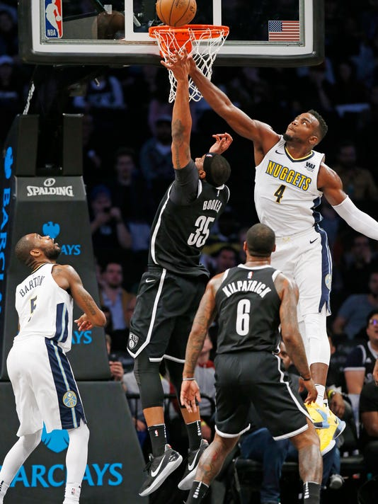Denver Nuggets forward Paul Millsap (4) defends as Brooklyn Nets forward Trevor Booker (35) shoots during the first half of an NBA basketball game, Sunday, Oct. 29, 2017, in New York. Nuggets guard Will Barton (5) and Nets guard Sean Kilpatrick (6) watch the play. (AP Photo/Kathy Willens)