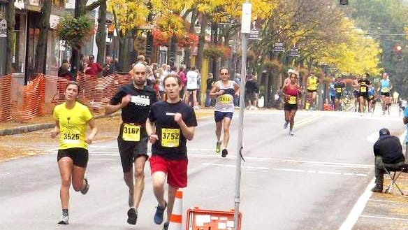 Runners head for the finish line of the Wineglass full and half marathons in the streets of Corning.