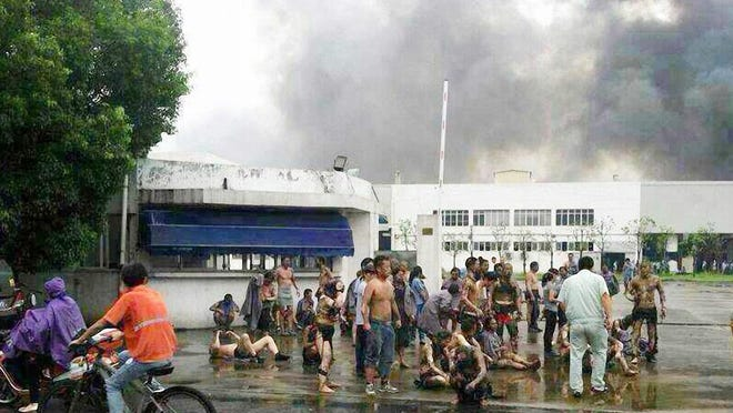 A picture taken with a mobile phone shows injured people waiting for medical help after an explosion at an automotive parts factory in Kunshan, Jiangsu province, China, on Aug. 2, 2014.
