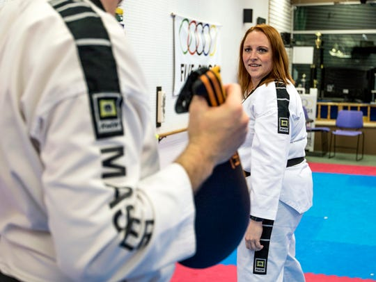 Alyssa Fencil, right, practices taekwondo with her