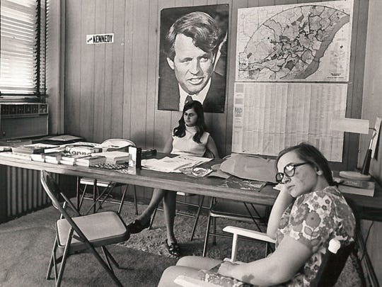 "Mary L. Marconi (left) and Frances Bazela, two volunteers at the Delaware ""Kennedy for President"" headquarters in Wilmington, stare into space and away from the picture of their candidate yesterday. Last night it was announced that the headquarters would close until definite word on the senator's condition is received and what plans may result. The announcement came from Ernest S. Wilson Jr., Kennedy's Delaware committee chairman. (June 6, 1968)"
