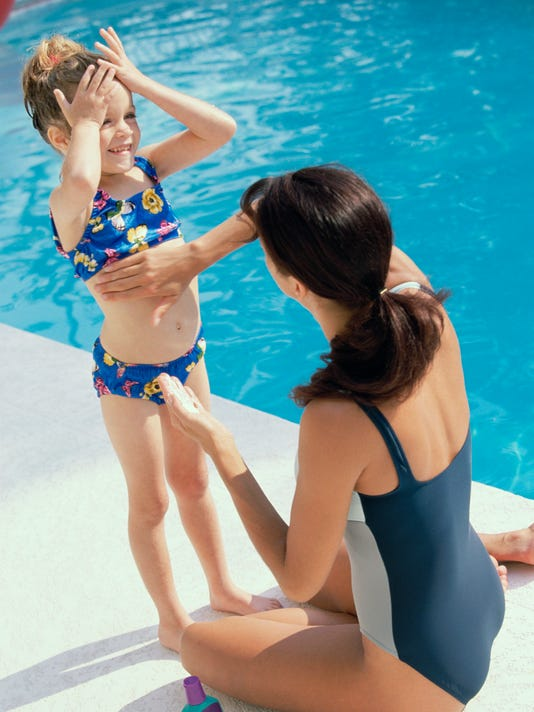 High angle view of a mother applying suntan lotion on her daughter