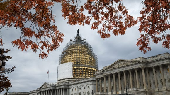 This Nov. 13, 2014, file photo shows the U.S. Capitol Dome, in Washington, surrounded by scaffolding for a long-term repair project.  Like a student who waited until the night before a deadline, lawmakers then resumed work to cram leftover business while avoiding a government shutdown.