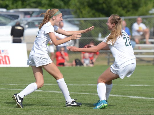 Novi's Avery Fenchel (left) is congratulated by teammate Julia Stadtherr after scoring the games only goal giving Novi a 1-0 victory over Grand Blamc to claim the Div. 1 state soccer title June 15 at Willinaston High School.