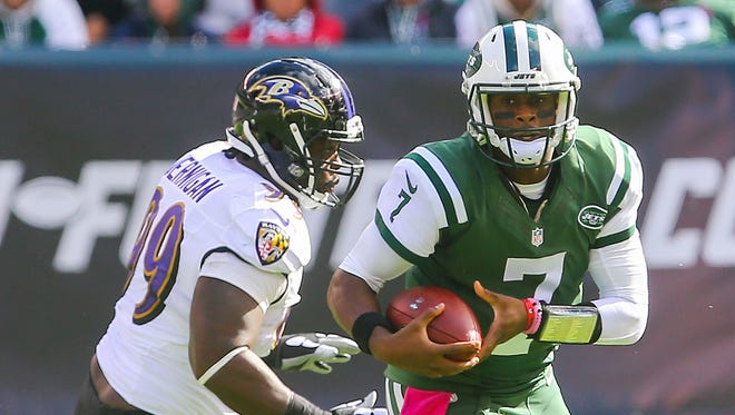 New York Jets quarterback Geno Smith (7) runs with the ball while being defended by Baltimore Ravens defensive end Timmy Jernigan (99)  during the first half of Sunday's game at MetLife Stadium.