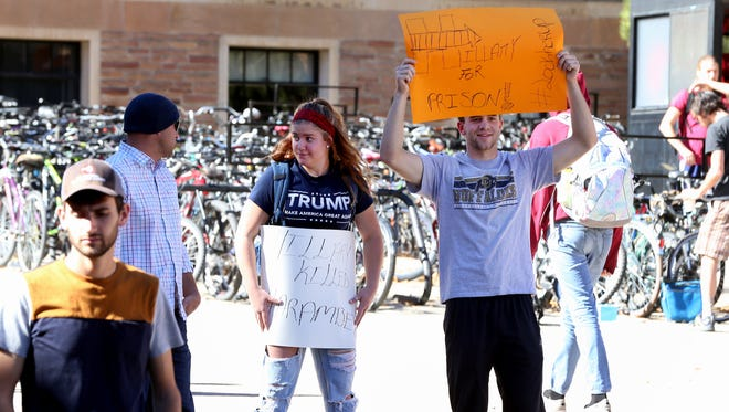 President-elect Donald Trump supporters holds campaign signs during a political rally for Hillary Clinton on Oct. 27, 2016, at the University of Colorado-Boulder in Boulder, Colorado. Political, nonpartisan and civic organizations push to get Colorado residents to return their mail-in ballots or vote on Election Day.