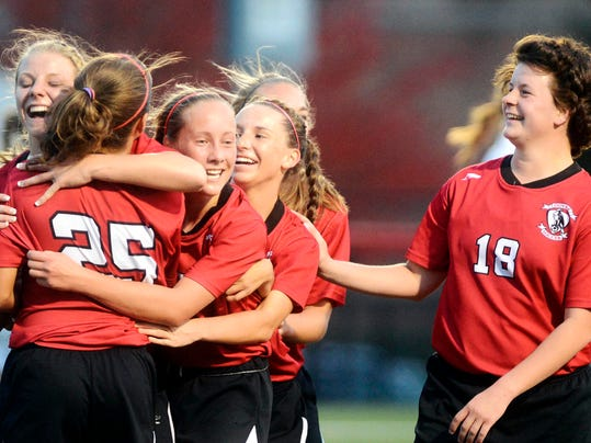 Dover players celebrate after beating four-time defending champion Dallastown, 3-1, to capture the YAIAA girls' soccer tournament title on Thursday at Susquehannock. (Daily Record/Sunday News -- Kate Penn)