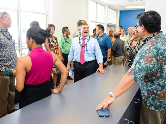 Gov. Eddie Calvo, center, reacts in laughter as he and others tour the Light Aircraft Commuter Facility near the Guam International Airport Authority terminal on Thursday, Oct. 1. A ribbon cutting was held to officially open the facility after GIAA spent $250,000 to renovate the old building to handle aircraft operations for lighter planes weighing 12,500 pounds or less.