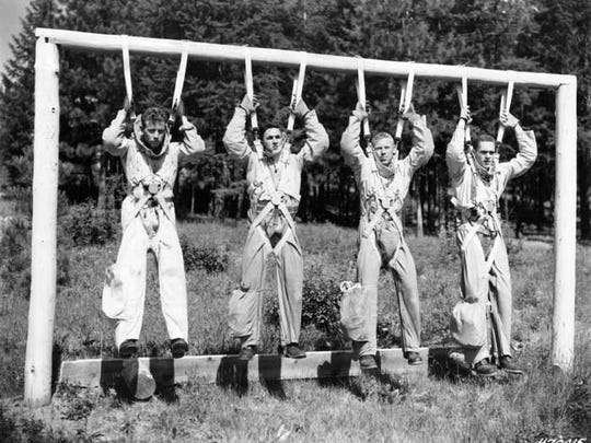 "Smokejumper squad leader Bill Carver and new trainees in 1952 practice fully suited ""mock-uprisers,"" which is designed to teach the ""planing"" maneuver and strengthen arm and shoulder muscles."