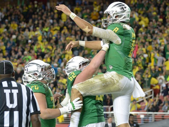 Teammates hoist Oregon QB Marcus Mariota after a touchdown.