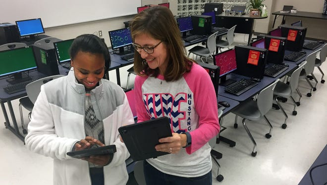 Campbell Street, left, and technology teacher Amy McAllister examine the iPads inside the computer lab at Dr. William Burrus Elementary School at Drakes Creek in Hendersonville on Monday, Jan. 4, 2016.