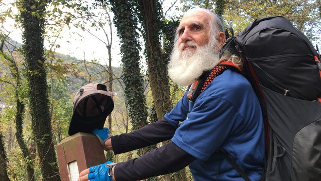 Dale Sanders, 82, stopped to kiss his last trail marker before becoming the oldest person to hike all 2,190 miles of the Appalachian Trail within a year.