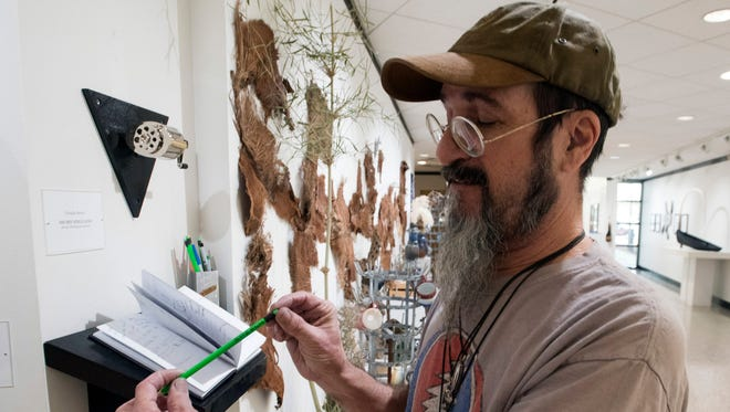 """Doug Reiser, adjunct professor at Pensacola State College, stands Thursday, Dec. 14, 2017, with his artwork at the Anna Lamar Switzer Center for Visual Arts in Pensacola. Reiser's anti-Trump contribution to the faculty art show, called """"I Alone Can Fix It,"""" has stirred controversy."""