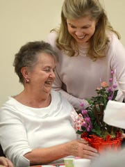 Suzie Johnson offers Marie Fortin a basket of flowers during a Valentine's Day celebration at the Northville Community Center a few years ago. Johnson is leaving her job as director of senior adult services for the Northville area.