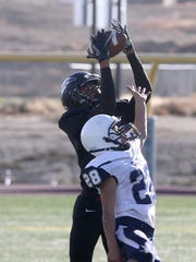 Shiprock's Adrian Gibson reaches over Silver's James Flores to catch a pass on Nov. 12 at Chieftain Stadium in Shiprock.