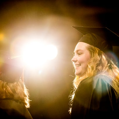 A graduate prepares to take the stage to get her diploma
