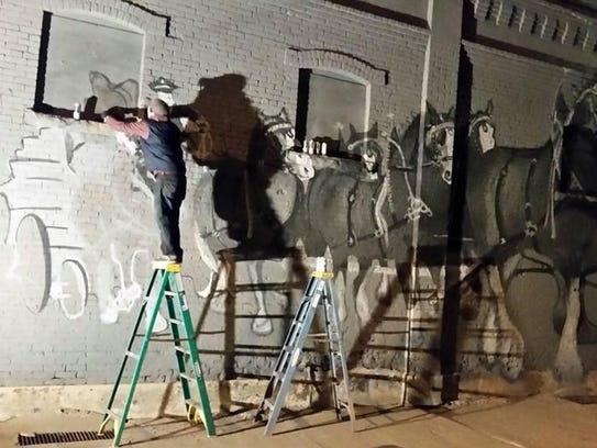 Work on the mural at Ed's Tavern stretched into the