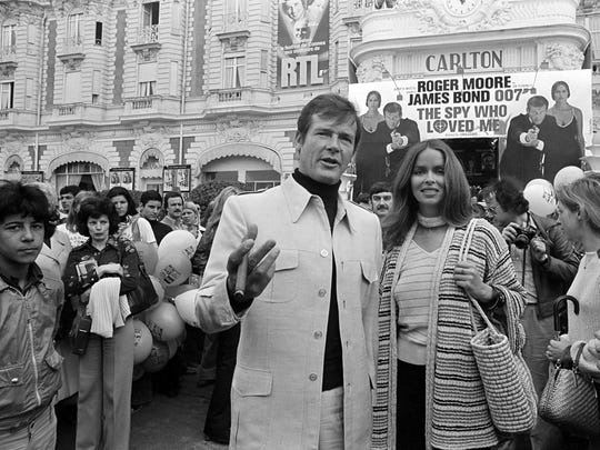 """In this May 20, 1977 file photo, Roger Moore, alias British secret agent James Bond, is accompanied by co-star Barbara Bach as they arrive for the screening of """"The Spy Who Loved Me"""" at the Cannes Film Festival on the French Riviera. Moore played Bond seven times over a dozen years. By the time he finished playing 007 in 1985's """"A View To A Kill,"""" he was 57, making him the oldest actor to portray Bond."""