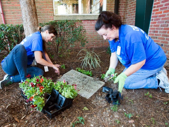 Florida Blue employees, Christine Burgos, left, and Janet Speranzi-Cannon, right, volunteer their time sprucing up the courtyards at O.J. Semmes Elementary School during the United Way Day of Caring Friday morning.