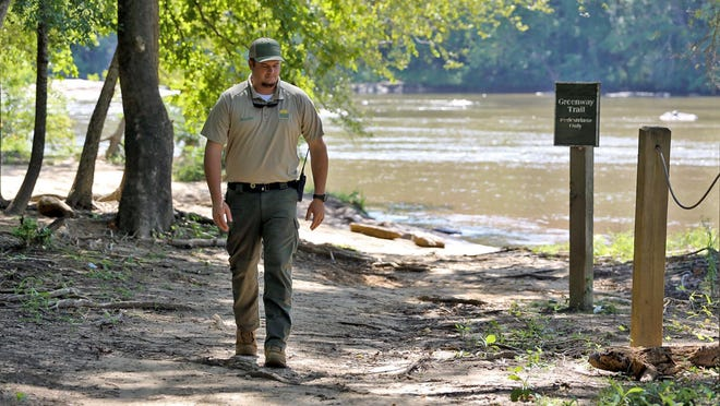 Ranger Lance Rollins takes a walk along the banks of the Broad River at the Broad River Greenway on Monday.