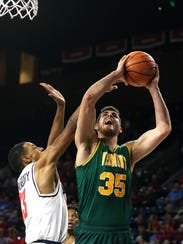 UVM's Payton Henson, right, goes for a layup in Wednesday