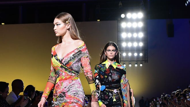 Models Gigi Hadid (L) and Kaia Gerber present creations for Versace fashion house during the Women's Spring/Summer 2019 fashion shows in Milan.