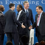 Republican presidential candidates from left, Jeb Bush, Ben Carson and New Jersey Gov. Chris Christie, right, during an economic forum, Saturday, Jan. 9, 2016, in Columbia, S.C.   Republican presidential candidates say the party must do more to convince poor Americans that conservative policies and not an active federal government, will expand economic opportunity. (AP Photo/Sean Rayford)