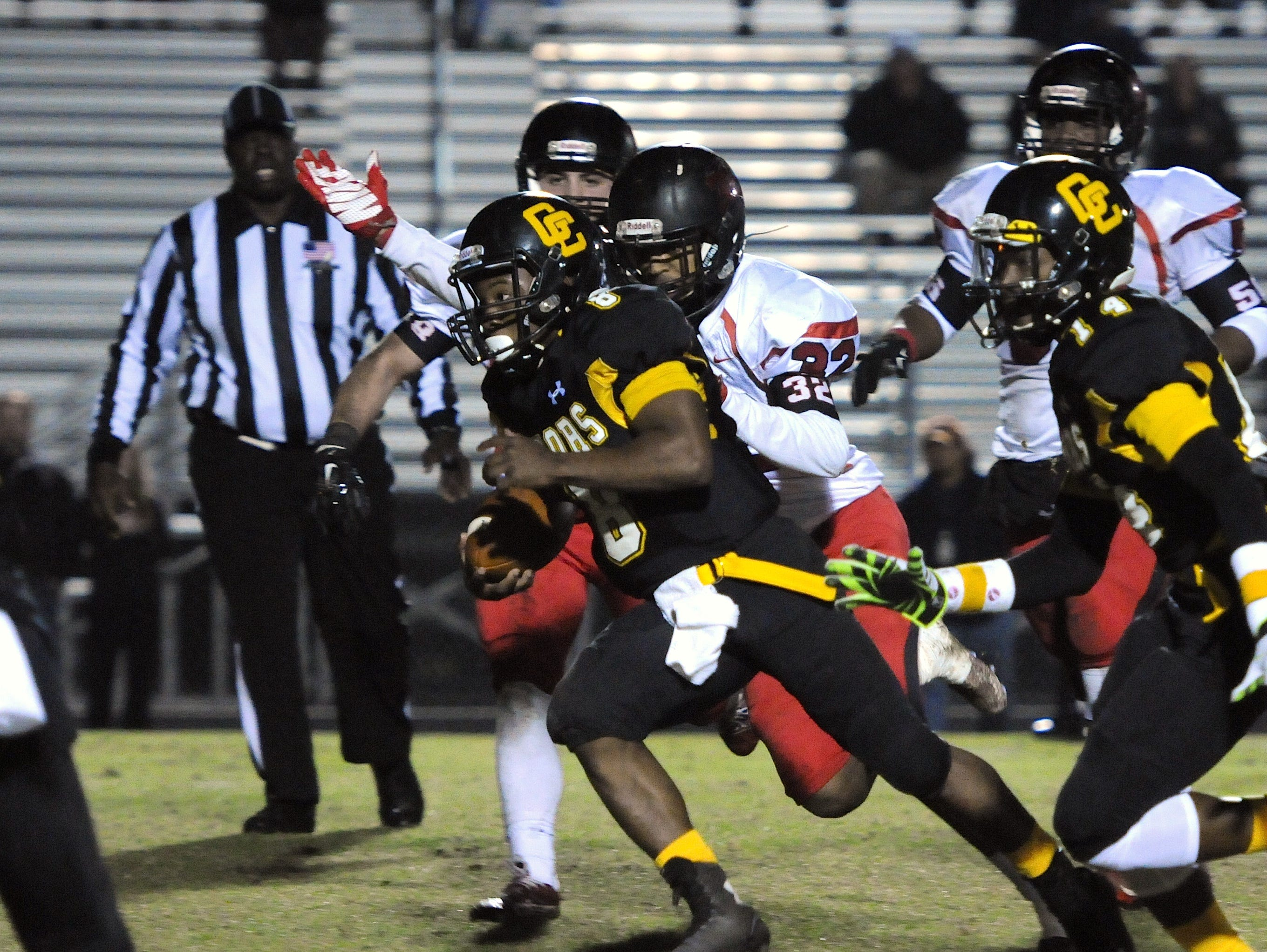 Goose Creek quarterback Dominique Jefferson (8) gains positive yardage up the middle before being tackled by Hillcrest's Parker Nichols (32).