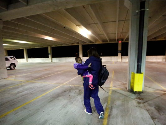 In this Jan. 27, 2015, photo, Virginia women's basketball coach Joanne Boyle walks with her adopted daughter Ngoty to her car after her day ends in Charlottesville, Va. Boyle had known for decades that she wanted to adopt a child, yet it would not be easy. She took 12 trips to Senegal over nearly three years, 14 in all. There were always obstacles. (AP Photo/Alex Brandon)