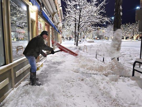 Tom Gorman shovels snow outside his business, Dean's