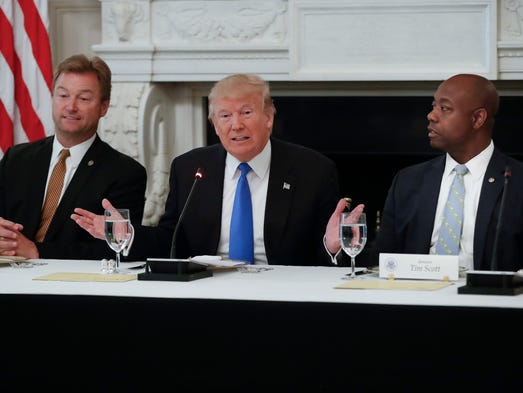 Trump, flanked by Sens. Dean Heller, R-Nev., and Tim
